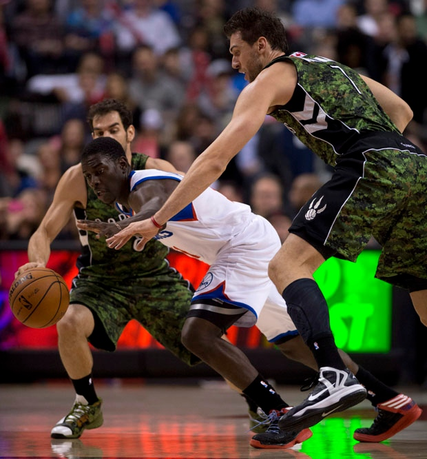 Toronto Raptors forward Andrea Bargnani, right, and Philadelphia 76ers guard Jrue Holiday chase a loose ball during first half NBA action in Toronto on Saturday, November 10, 2012. THE CANADIAN PRESS/Frank Gunn