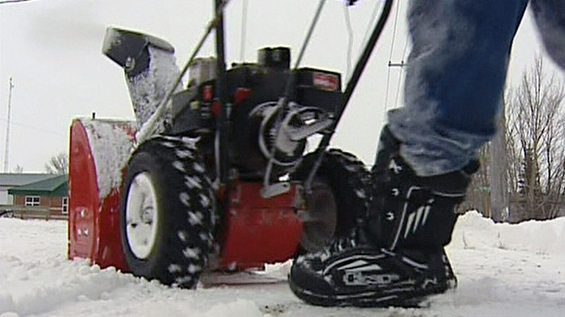 Getting a head start on a forecasted blizzard, a man uses a snowblower on the sidewalk in front of his home in Elie, Manitoba, Saturday, Nov. 10, 2012.