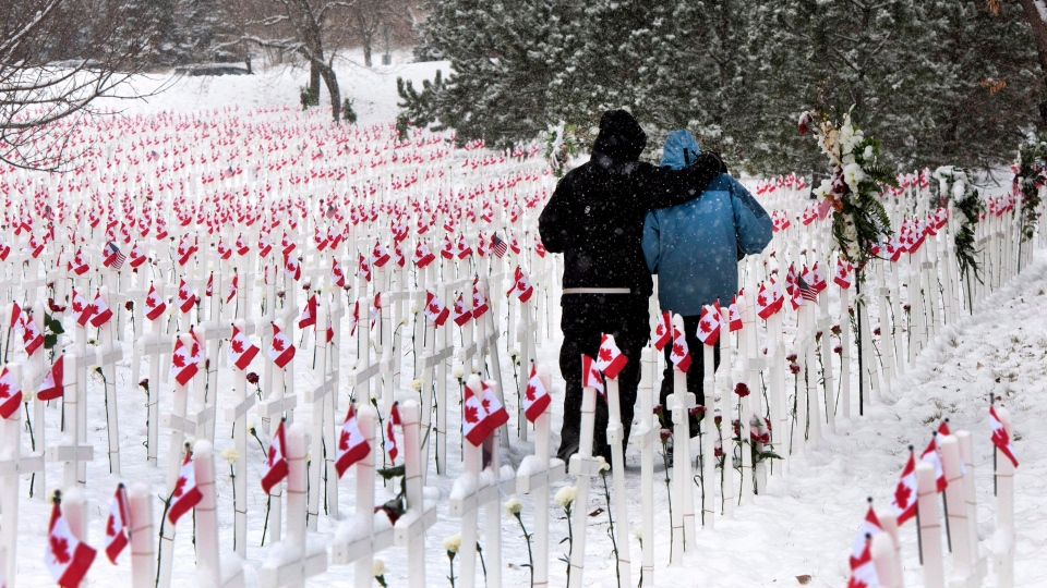 Despite heavy snowfall, two people walk through the Field of Crosses in Calgary, Alberta, on Thursday, Nov .8, 2012. (Larry MacDougal / THE CANADIAN PRESS)