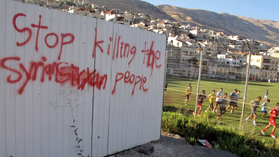 Boys train in a soccer field next to a graffiti against the killing in Syria, in Majdal Shams, Golan Heights, Wednesday, Aug. 8, 2012. (AP / Diaa Hadid)
