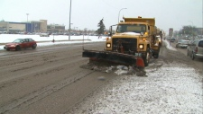 Snow plow drives along a slush-filled road
