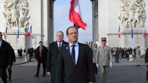 French President Francois Hollande, centre right, and French Prime Minister Jean Marc Ayrault, centre left, leave the Arc de Triomphe after the Armistice Day ceremonies in Paris, Sunday, Nov. 11, 2012. (AP Photo/Philippe Wojazer, Pool)