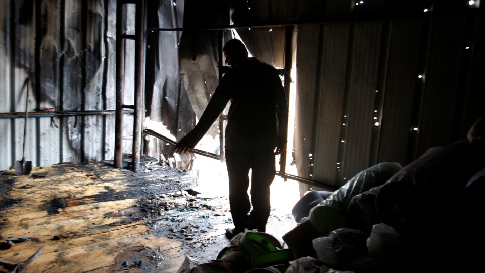 A Palestinian stands in a factory hit by an Israeli tank shell in Beit Hanoun, northern Gaza Strip, Sunday, Nov. 11, 2012. (AP Photo/Hatem Moussa)