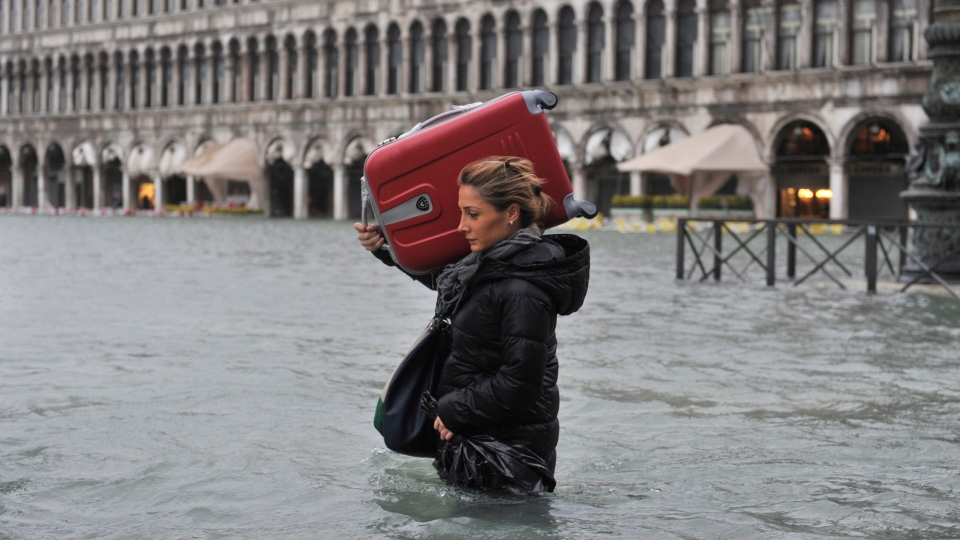 A tourist crosses flooded St. Mark's Square in Venice, Italy, Sunday, Nov. 11, 2012. (AP / Luigi Costantini)