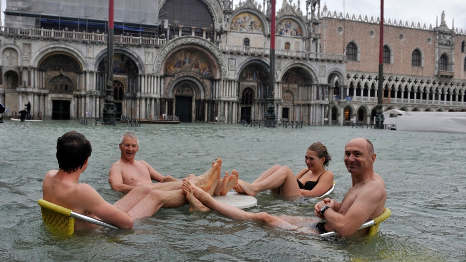 People sit at the table of a bar in a flooded St. Mark's Square in Venice, Italy on Sunday, Nov. 11, 2012. (AP / Luigi Costantini)
