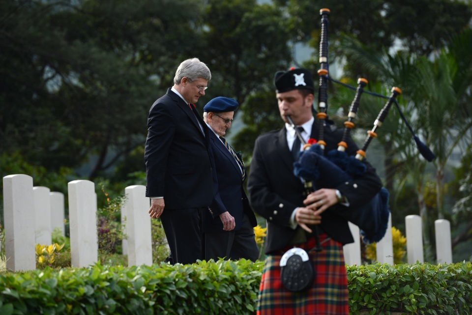 Prime Minister Stephen Harper walks with Hong Kong Veteran Arthur Kenneth Pifher, 91, of Grimsby, Ont., as they take part in a Remembrance Day ceremony at Sai Wan War Cemetery in Hong Kong on Sunday, November 11, 2012. (Sean Kilpatrick / THE CANADIAN PRESS)