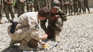Warrant Officer Tim MacCormac of the Canadian Contribution Training Mission - Afghanistan demonstrates how to place a charge to dispose of an unexploded ordnance during a class with Afghan National Army (ANA) soldiers in Kabul, Afghanistan, June 28, 2011. (DND / Master Cpl. Rory Wilson)