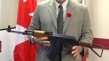 Sgt. Shinder Kirk shows off an AK-47 assault rifle investigators believe was to be used in a murder conspiracy in Cranbrook, B.C. Nov. 3, 2010. (CTV)