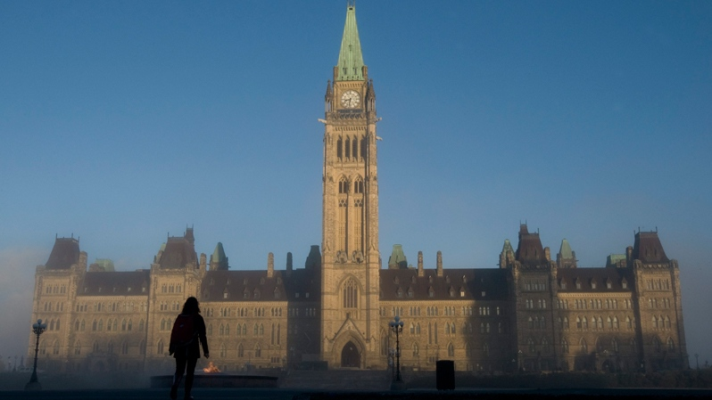 Sun illuminates the Peace Tower as a visitor makes their way onto Parliament Hill in Ottawa, Wednesday, Nov. 3, 2010. (Adrian Wyld / THE CANADIAN PRESS)