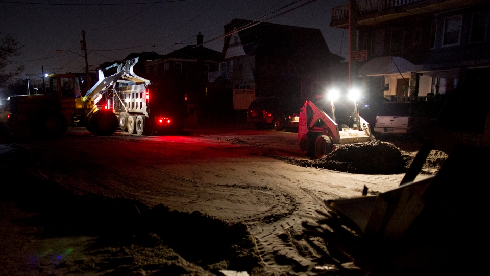 A front loader works to remove sand and debris as night falls on the Rockaway neighborhood in the Queens borough of New York, Sunday, Nov. 11, 2012. (AP / Craig Ruttle)