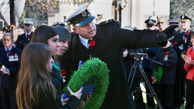 Memorial Cross recipients Jenna, Makayla and Michael Curwin prepare to lay a wreath at the Cenotaph during Remembrance Day ceremonies at the Grand Parade in Halifax on Sunday, Nov. 11, 2012. (Andrew Vaughan / THE CANADIAN PRESS)