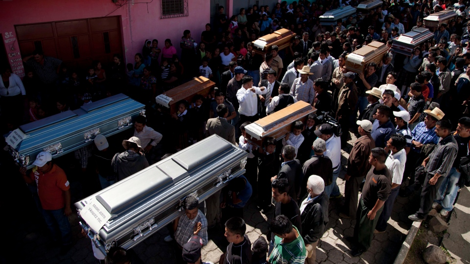 People carry the coffins with the remains of 10 members of the Vasquez family who died when an earthquake struck San Cristobal Cucho, Guatemala, Friday, Nov. 9, 2012. (AP / Moises Castillo)
