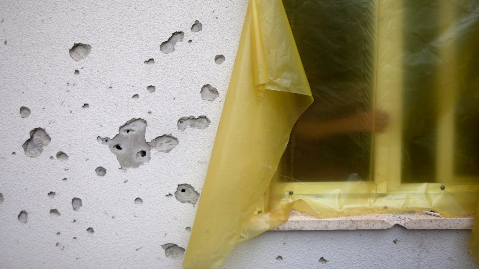 Mortar shell marks are seen on a wall as a person closes a broken window of his house in a community along the Israel Gaza border, Israel, Sunday, Nov. 11, 2012. (AP / Ariel Schalit)