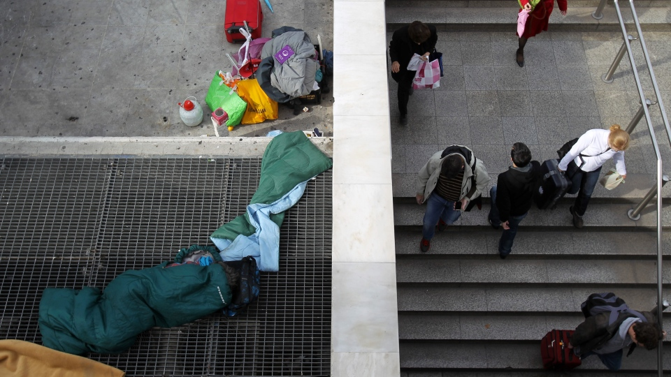 A homeless person sleeps on a metro ventilation grill as commuters enter Syntagma station in Athens, Monday, Nov. 12, 2012. (AP / Thanassis Stavrakis)