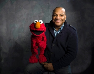 'Sesame Street' muppet Elmo and puppeteer Kevin Clash poses for a portrait in the Fender Music Lodge during the 2011 Sundance Film Festival to promote the film 'Being Elmo' in Park City, Utah. (AP / Victoria Will)
