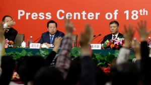 China's Minister for Environmental Protection Zhou Shengxian, center, and Ministry of Housing and Urban-rural Development Jiang Weixin, right, look at reporters raise their hands to ask questions during a press conference at the media center of the 18th Chinese Communist Party Congress in Beijing Monday, Nov. 12, 2012. (AP Photo/Lee Jin-man)