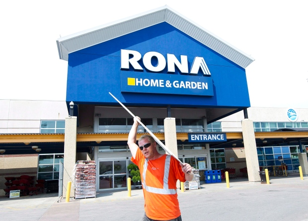 A man carries building supplies from a Rona store