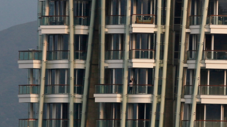 A worker cleans a window at the luxury residential building 'Opus Hong Kong,' designed by Frank Gehry in Mid-Levels East of Hong Kong, Tuesday, Nov. 13, 2012. (AP / Kin Cheung)