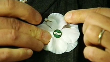 Brenda Vellino, with the Ottawa Poppy Coalition, pins a white poppy on her shirt which she has been promoting as a way to remember civilians who have died in war.