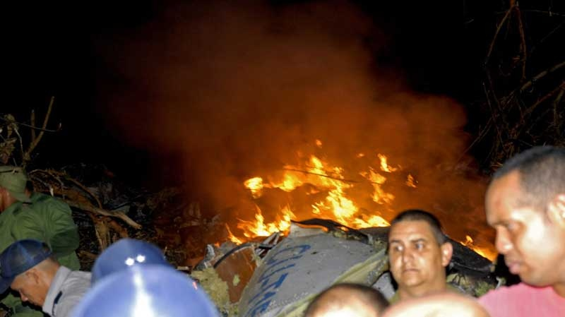 Flames emerge from the wreckage of a Cuban airliner as Police officers and residents look on after it crashed near the village of Guasimal in Santi Spiritus province, Cuba, Thursday Nov. 4, 2010.(AP Photo/Escambray, Prensa Latina)