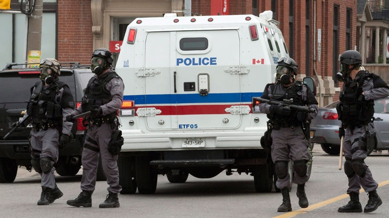 Police officers in riot gear guard a street near a temporary detention centre in Toronto, Sunday, June 27, 2010. (Jacques Boissinot / THE CANADIAN PRESS)