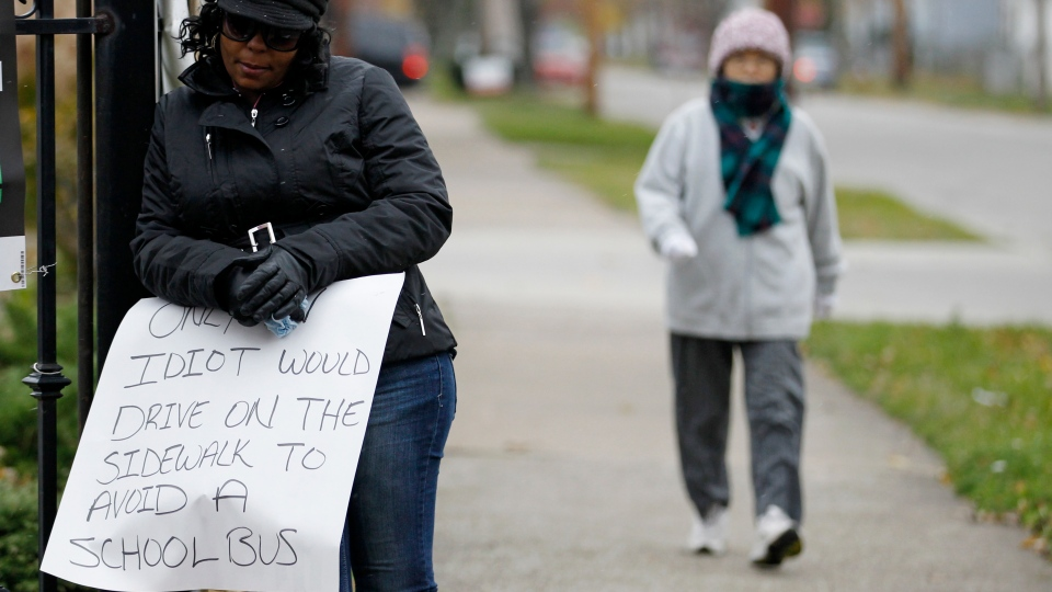 A woman walks by as Shena Hardin, left, holds up a sign to serve a highly public sentence in Cleveland, Tuesday, Nov. 13, 2012. (AP / Tony Dejak)