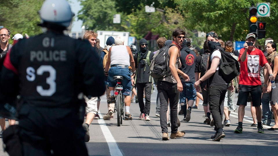 Protesters flee from in front of the Hydro Quebec building as riot police move in and clear the area during an anti-government protest in Montreal, Quebec on Wednesday, August 8, 2012. (Peter McCabe / THE CANADIAN PRESS)