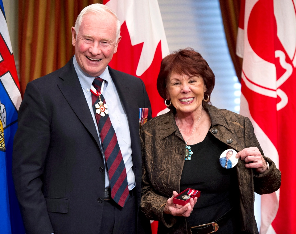 Colleen Klein, wife of former Alberta Premier Ralph Klein, shows a Klein election badge after accepting the Order of Canada from Governor General David Johnston on behalf of her husband in Calgary, Alberta on Tuesday, Nov. 13, 2012. (Larry MacDougal / THE CANADIAN PRESS)