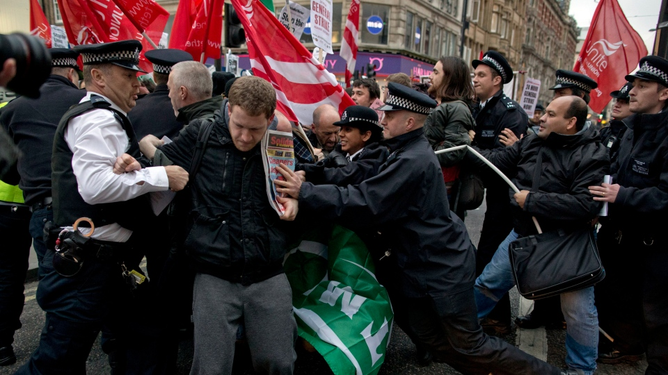 Police officers try to push protesters back onto the pavement after they blocked traffic on Oxford Street, London, whilst taking part in a picket and demonstration they said was over dismissals of 28 workers employed by contractors on the Crossrail transport project, for being trade union members, Wednesday, Nov. 14, 2012.  (AP / Matt Dunham)