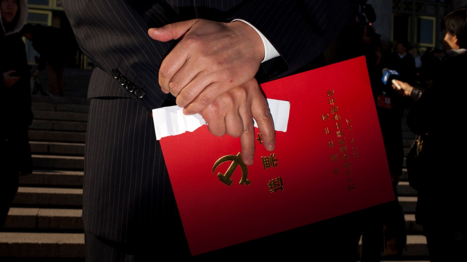 A Chinese Communist Party delegate holds a red voting ticket holder while leaving the Great Hall of the People with other delegates after the closing ceremony for the 18th Communist Party Congress in Beijing Wednesday, Nov. 14, 2012.  (AP / Alexander F. Yuan)