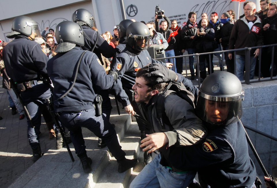 Riot police apprehend a protestor during a general strike in Madrid, Spain, Wednesday, Nov. 14, 2012. (AP / Andres Kudacki)