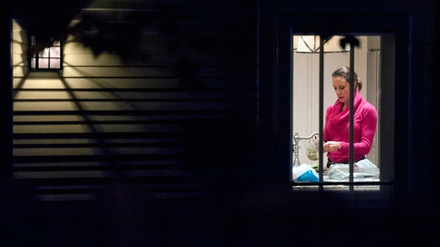 Paula Broadwell is visible through a window in the kitchen of her brother's house in Washington on Tuesday, Nov. 13, 2012. (AP Photo/Cliff Owen)