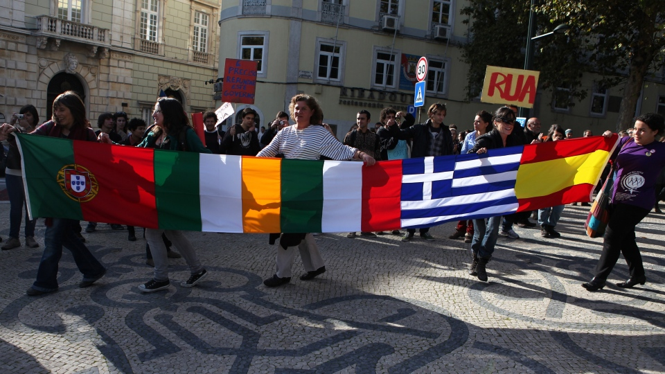Protestors carry the flags of Portugal, Ireland, Italy, Greece and Spain, from left to right, while marching towards the Portuguese parliament in Lisbon during a general strike Monday, Nov. 14, 2012.  (AP / Joao Henriques)