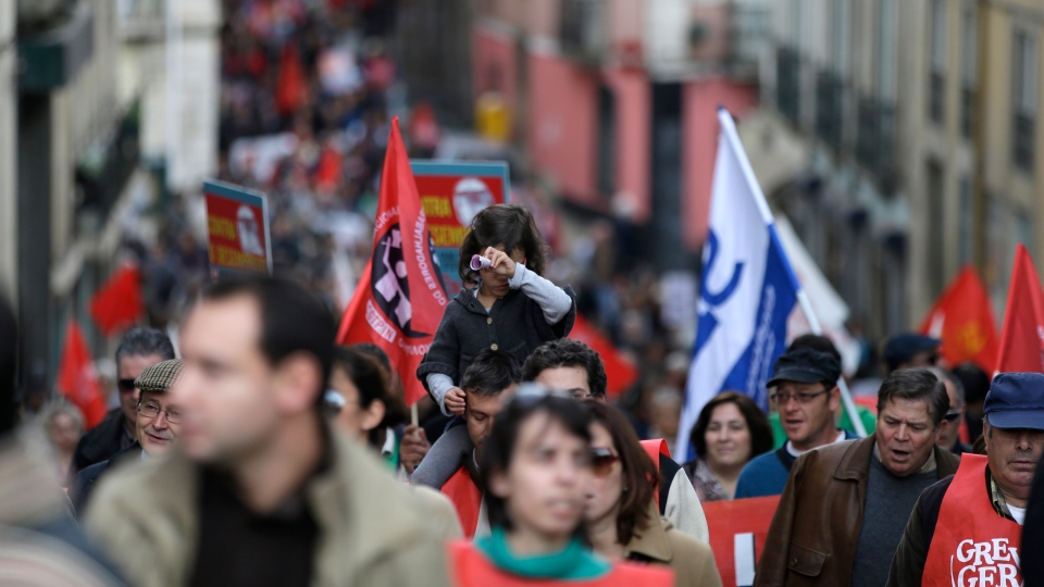 A demonstrator carries a young girl on his shoulders while marching towards the Portuguese parliament in Lisbon during a general strike Monday, Nov. 14 2012. (AP / Armando Franca)