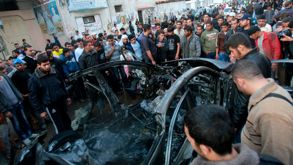 People look at a wreckage of the car in which was killed Ahmed Jabari, head of the Hamas military wing in Gaza City, on Wednesday, Nov. 14, 2012. (AP / Adel Hana)