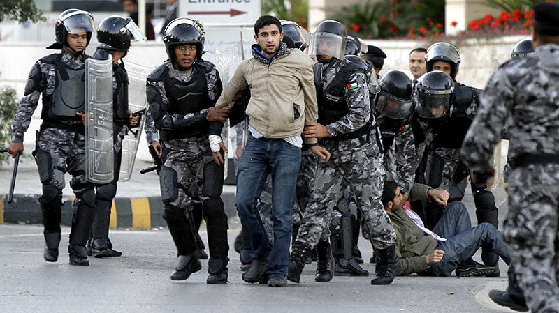 Jordanian policemen detain protesters blocking a main road during a demonstration against a rise in fuel prices in downtown Amman, Jordan, Wednesday, Nov. 14, 2012. (AP / Raad Adayleh)
