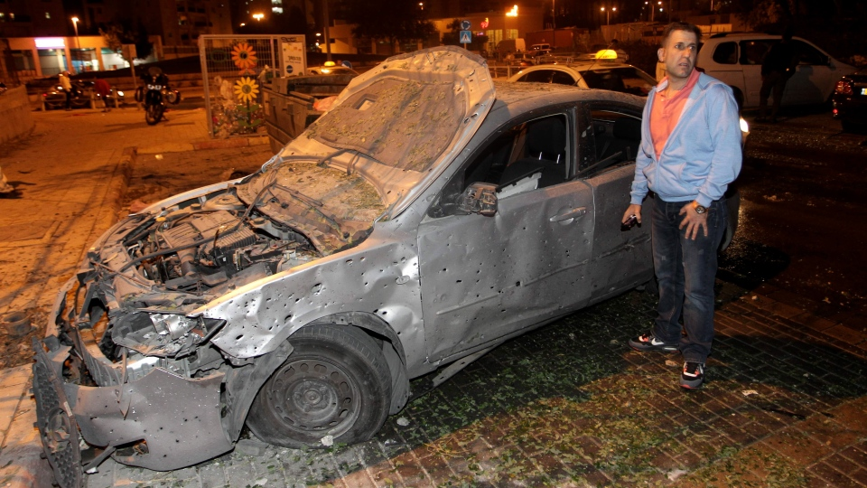 An Israeli man stands next to a car damaged by a rocket fired by Palestinian militants from the Gaza Strip in the southern Israeli city of Beersheva, Wednesday, Nov. 14, 2012. (AP / Ilan Assayag)