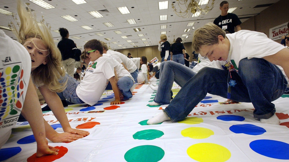 Some 450 high school students play Twister on 180 mats in what they hope will set a world record for the largest Twister game board, Sunday, Oct. 7, 2007. (The Forum / Jay Pickthorn)
