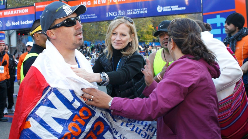 New York Road Runners president Mary Wittenberg, center, congratulates Chilean miner Edison Pena as Pena joins his wife, Angelica Alvarez, right, after Pena finished the New York City Marathon in New York, Sunday, Nov. 7, 2010. (AP / Kathy Willens)
