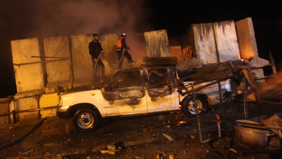 A Palestinian Hamas policeman, left, and a firefighter try to extinguish a fire after an Israeli airstrike in Shati, Gaza city, Thursday, Nov. 15, 2012. (AP / Ashraf Amra)