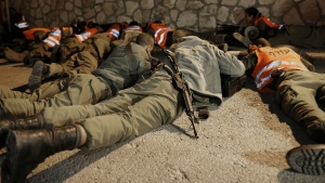 Israeli soldiers take cover as an air raid siren warns of incoming rockets before the funeral of Aaron Smadja, one of the three Israelis killed by a rocket fired from Gaza, at a cemetery in the southern town of Kiryat Malachi, Thursday, Nov. 15, 2012. (AP  / Tsafrir Abayov)
