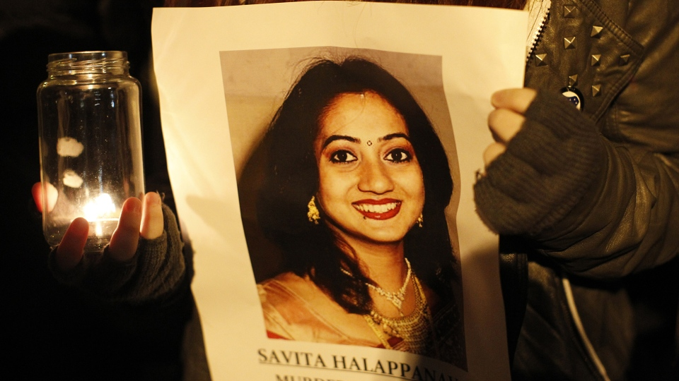 A woman holds a picture of Savita Halappanavar during a candle lit vigil outside Belfast City Hall, Northern Ireland, Thursday, Nov. 15, 2012. (AP / Peter Morrison)