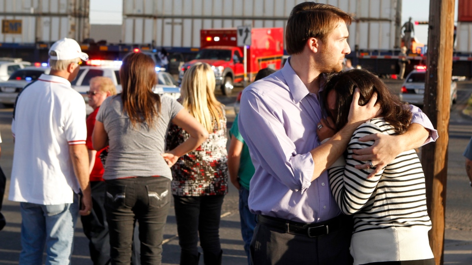 Bystanders react as emergency personnel work the scene where a trailer carrying wounded veterans in a parade was struck by a train in Midland, Texas, Thursday, Nov. 15, 2012. (James Durbin / Reporter-Telegram)