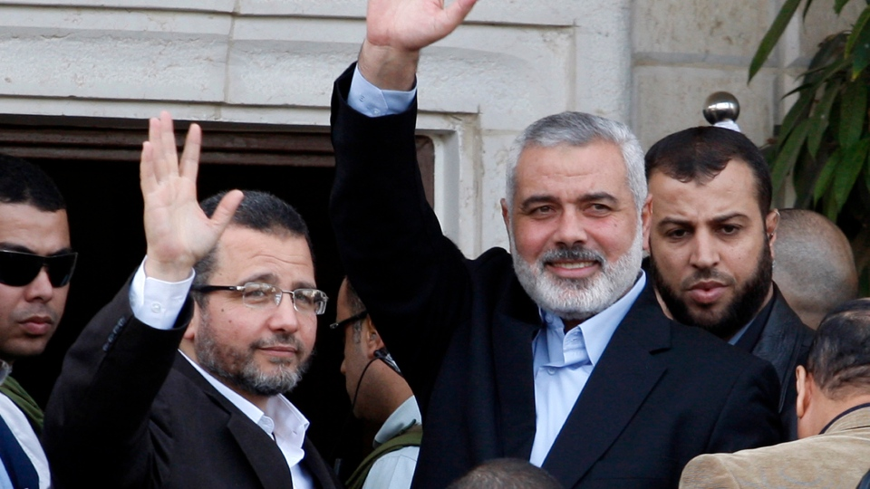 Gaza's Hamas Prime Minister Ismail Haniyeh, right, and Egyptian Prime Minister Hesham Kandil, left, wave to the crowd as they meet in Gaza City, Friday, Nov. 16, 2012.(AP Photo/Adel Hana)