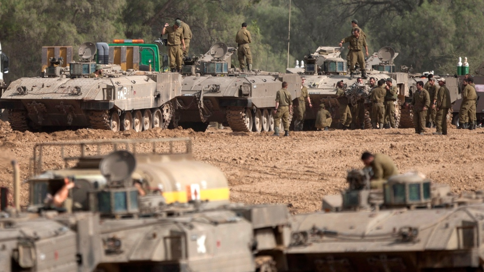 Israeli soldiers work on their a tanks in a staging ground near the border with Gaza Strip, southern Israel, Friday, Nov. 16, 2012. (AP / Ariel Schalit)
