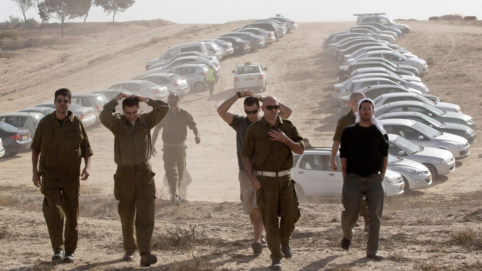 Israeli military reservists arrive at a gathering point in Mishmar Hanegev, southern Israel, Friday, Nov. 16, 2012. The Israeli government approved on Thursday the mobilization of up to 30,000 reservists for a possible ground incursion into Gaza. (AP / Ilan Assayag)