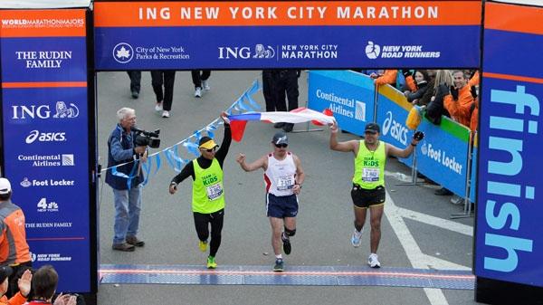 Chilean miner Edison Pena, center, crosses the finish line at the New York City Marathon in New York, Sunday, Nov. 7, 2010. (AP / Seth Wenig)