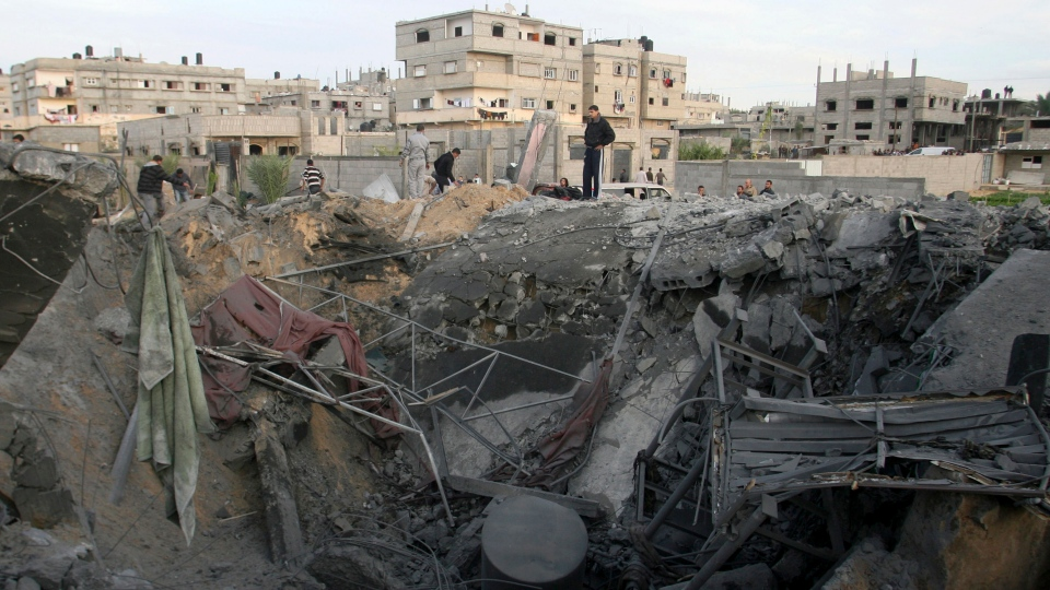 Palestinians stand on the rubble of the destroyed house of Hamas militant Mohammad Abu Shmala, following an Israeli air strike in Rafah, southern Gaza Strip, Friday, Nov. 16, 2012. (AP / Eyad Baba)