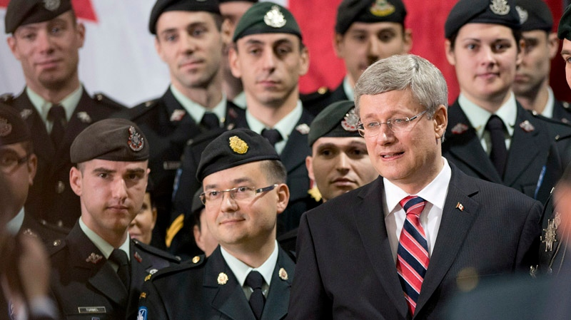 Prime Minister Stephen Harper walks past Canadian soldiers Friday, November 16, 2012 at the Citadelle in Quebec City. Harper was announcing the reconstruction of the historic drill hall that was destroyed in a fire in 2008. THE CANADIAN PRESS/Jacques Boissinot