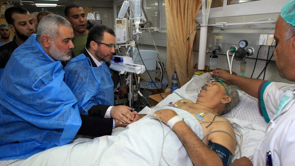 Gaza's Hamas Prime Minister Ismail Haniyeh, left, and Egyptian Prime Minister Hesham Kandil, second left, visit a man wounded in an Israeli strike, at the hospital in Gaza City, Friday, Nov. 16, 2012. (AP / Mahmud Hams)